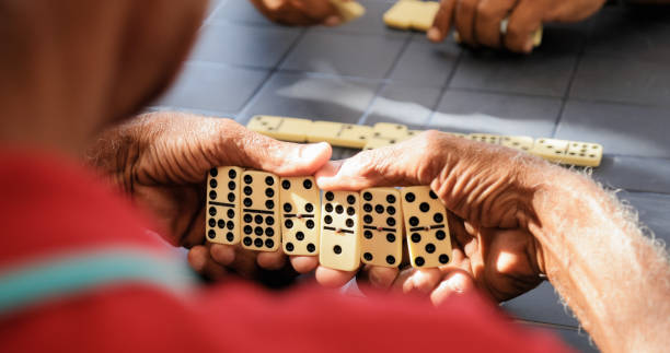 Black Retired Senior Man Playing Domino Game With Friends stock photo