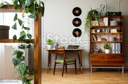 istock Black retro typewriter on a unique wooden desk, a mid-century modern chair and a renovated bookcase in a hipster home office interior. Real photo. 1057279940