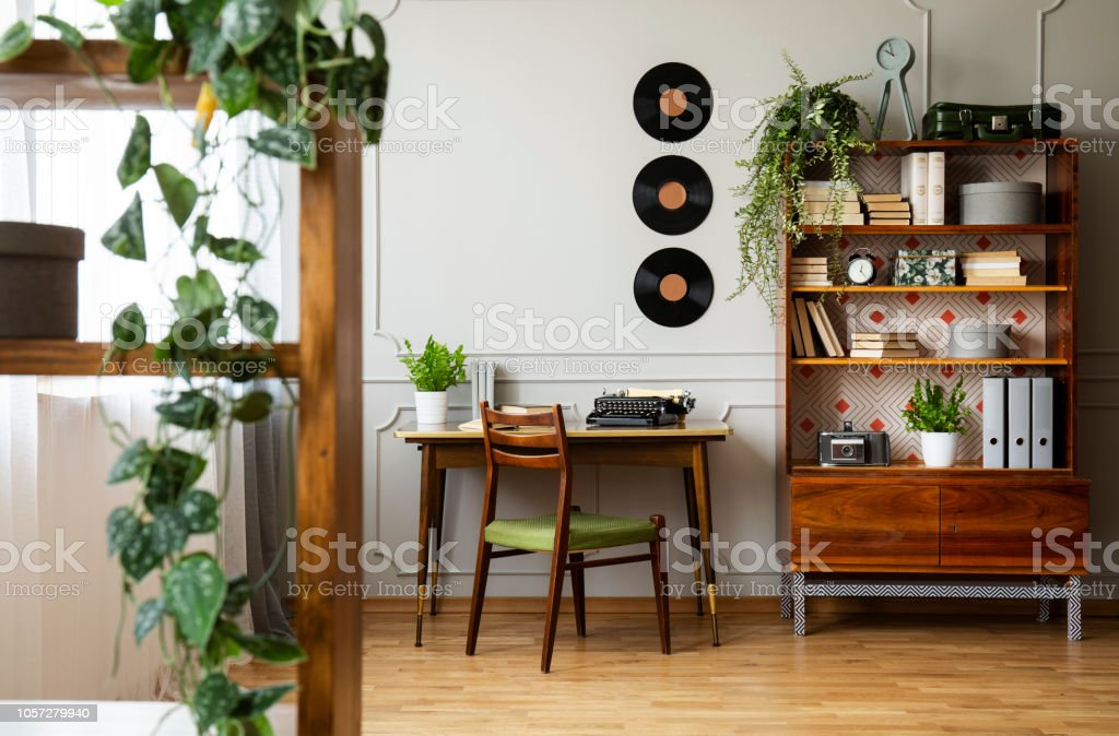 Black retro typewriter on a unique wooden desk, a mid-century modern chair and a renovated bookcase in a hipster home office interior. Real photo. – zdjęcie