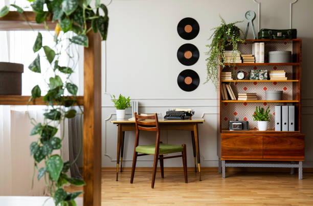 Black retro typewriter on a unique wooden desk, a mid-century modern chair and a renovated bookcase in a hipster home office interior. Real photo. stock photo