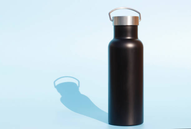 A black reusable bottle for water on blue background stock photo