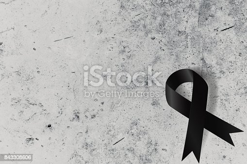 istock Black ribbon on concrete wall with space for text 843308606