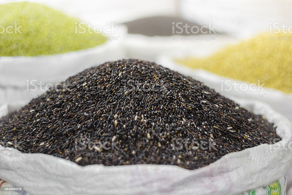 Black rice and other grains in bags on oriental market stock photo