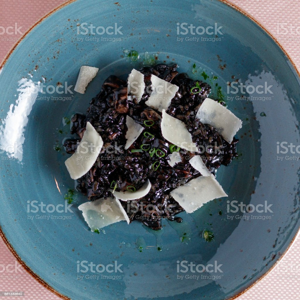 Black risotto with Parmesan on a blue plate stock photo