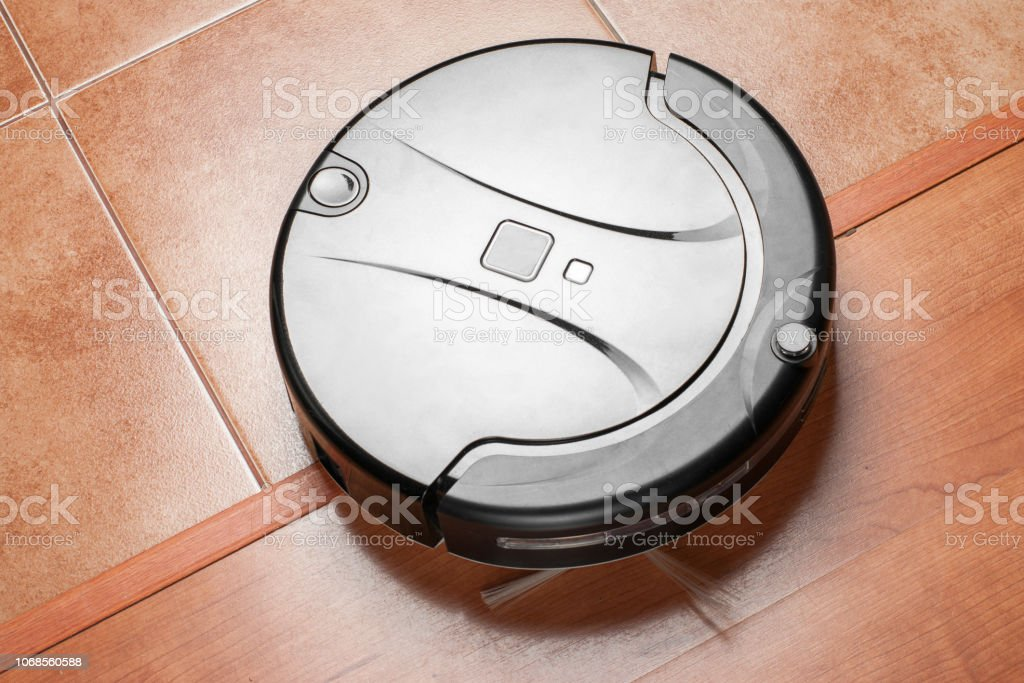 Black robotic vacuum cleaner, modern smart appliance, perfect automated floor cleaning tool to help automate housekeeping stock photo