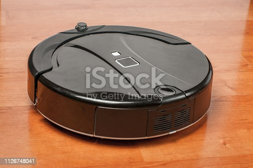 istock black robotic vacuum cleaner runs on laminate floor closeup. robot controlled by voice commands for direct cleaning. modern technology of smart cleaning 1126748041