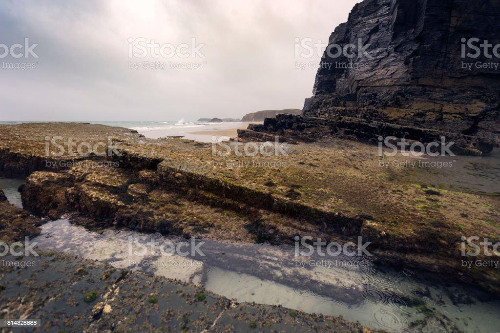 Black rocks in a wet beach stock photo