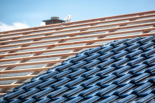Black roof of burnt tiles under construction, roof paver