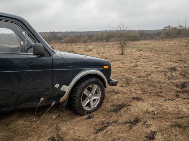schwarzrussischen geländewagen lada niva 4x4 (vaz 2121/21214) parkte auf dem feld. - lada niva stock-fotos und bilder
