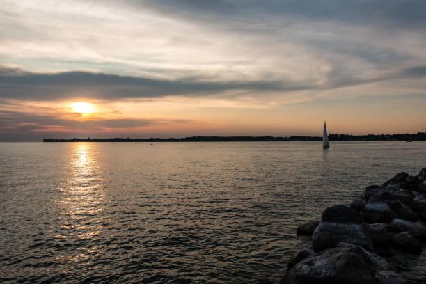 Schwarzes Segelboot und ein kleiner schwarzer Landspieß ins Wasser und ein goldener Sonnenuntergang – Foto