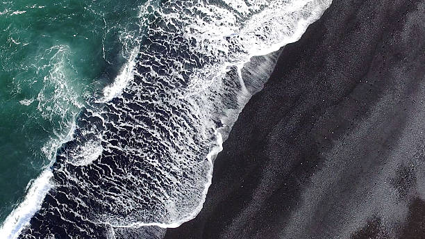 black sand beach at iceland Cold ocean waves washing down the sand from the perfectly gradient beach, making a lot of ocean foam in the process. Colors of the sand go from the light gray to black. black sand stock pictures, royalty-free photos & images