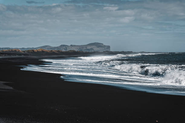 Black Sand Beach Black sand beach with waves in Vik. black sand stock pictures, royalty-free photos & images