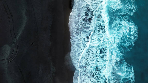 Black sand beach Aerial view of turquoise colored wave splashing to black sand beach black sand stock pictures, royalty-free photos & images