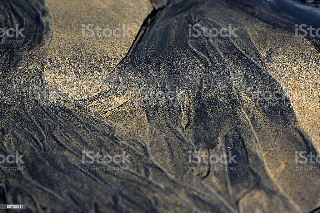 schwarzer Sand am Strand stock photo
