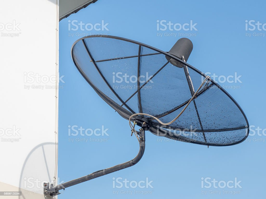 Black satellite dish mounted on a wall outside the house stock photo