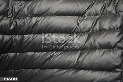 637513166istockphoto Black satin fabric with down filling and gold reflection from a warm female down jacket with lines along the entire fabric. 1146008698