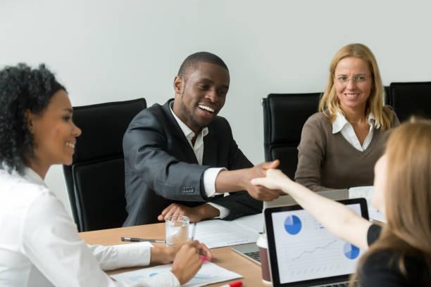 Negro satisfecho a empresario apretón de manos nuevo blanco pareja femenina concluir contrato - foto de stock