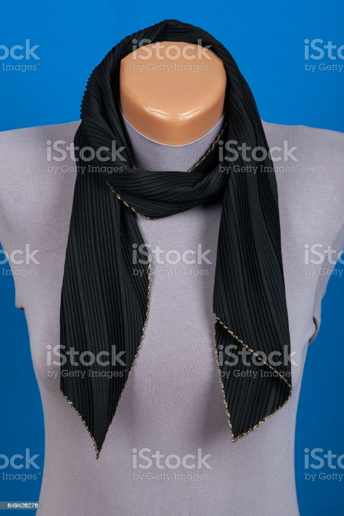 Black scarf on mannequin isolated on blue background. stock photo
