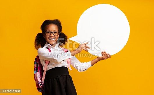 istock Black Schoolgirl Holding Speech Bubble In Studio 1174502534