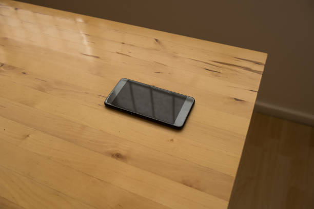 black screen reflection smartphone on wooden desk in bright office in the afternoon - green screen background stock photos and pictures