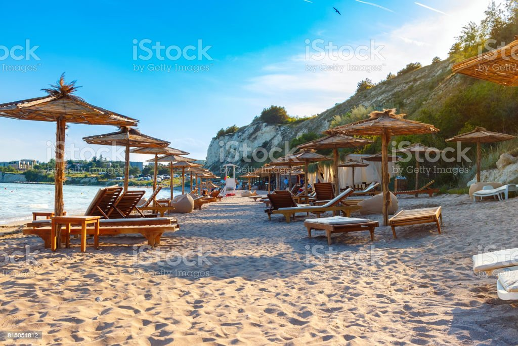 Black sea coast, sand beach with sunbeds and straw umbrellas, summer sea rest concept stock photo