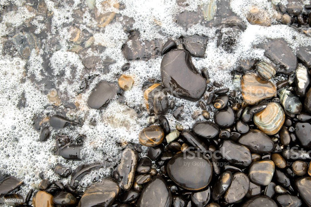Black sea stones background. Glossy round river rocks and wave surfing, Thailand. wanderlust and unplugged. Top view. Close up. royalty-free stock photo