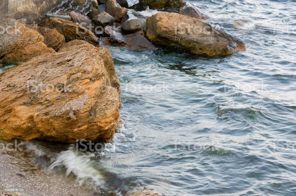 Black Sea. Water with no waves and little boat far away. Big stone in...