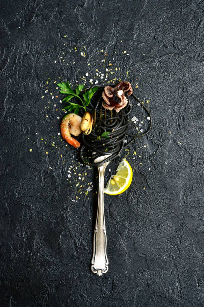 black seafood spaghetti on fork - food styling stock photos and pictures