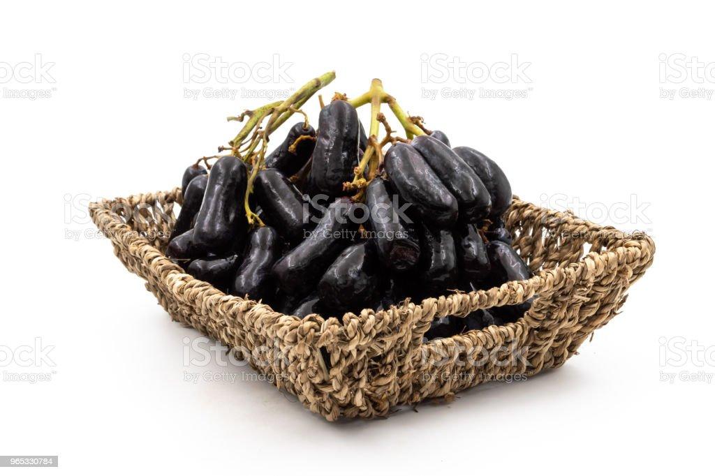 Lune sans pépins noir drops de raisins ou de raisin de doigts de sorcière en panier sur fond blanc - Photo de Agriculture libre de droits
