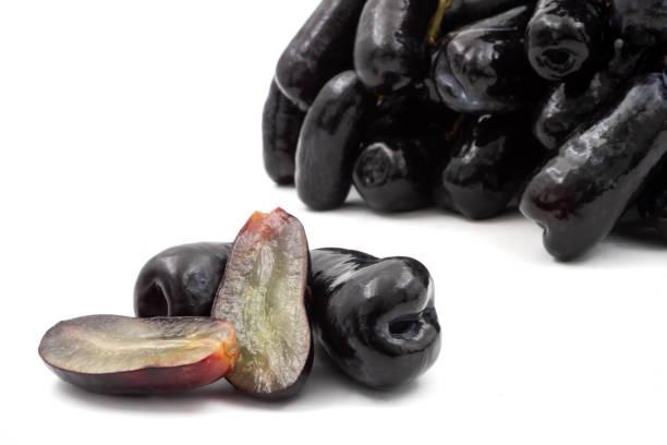 Lune sans pépins noire gouttes de raisins ou de raisin de doigts de sorcière sur fond blanc - Photo