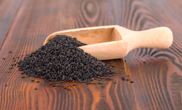 black sesame in spoon on wooden surface. stock photo