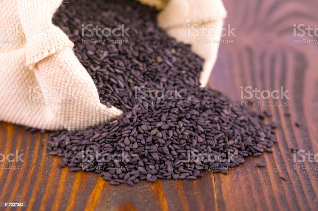 black sesame in the bag on wooden surface. stock photo