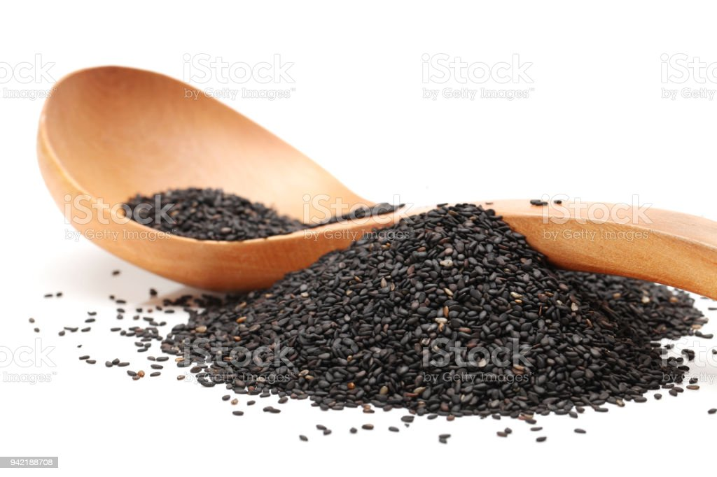 Black sesame in wooden spoon isolated on white background stock photo