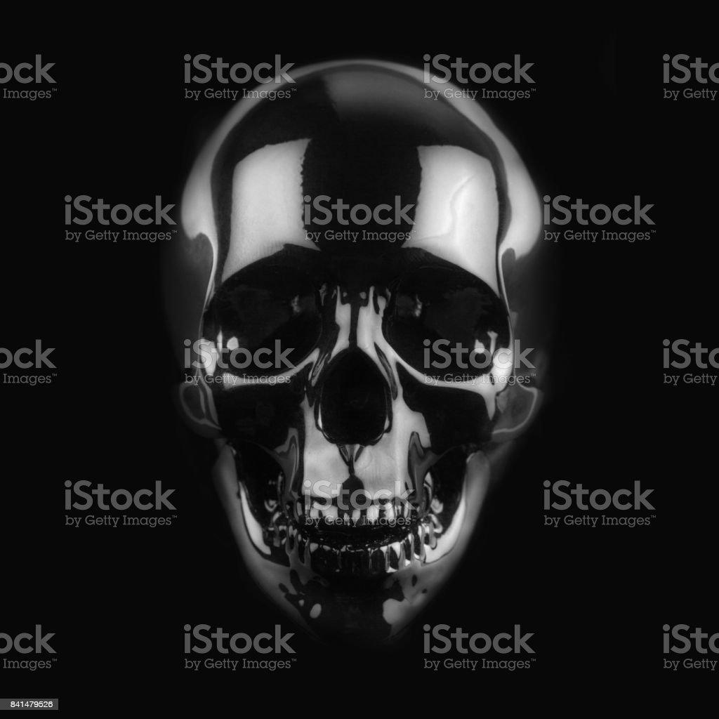 black shiny skull on dark background stock photo