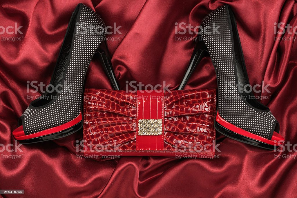 Black shoes and purse lying on the red satin stock photo