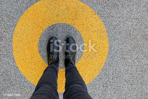 Black shoes standing in yellow circle on the asphalt concrete floor. Comfort zone or frame concept. Feet standing inside circle