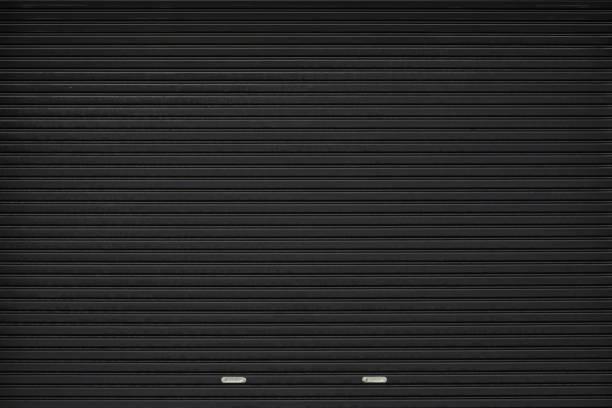 black shutter door with stainless steel holder. grunge black metal foldable door background and texture. - portão imagens e fotografias de stock