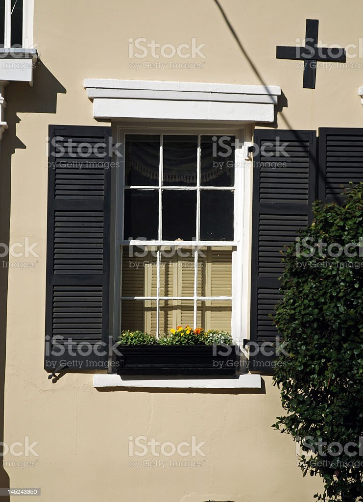 Black Shuttered Windows with Cross and Window Box royalty-free stock photo