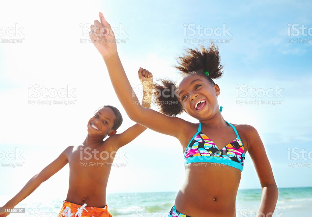 Black siblings smiling and jumping in front of the ocean stock photo