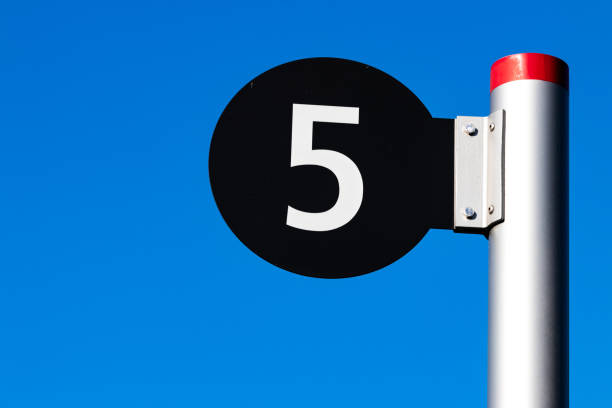 Black sign with a white number 5 on a steel post stock photo