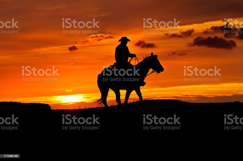 Black silhouette of a cowboy riding a horse at sunset stock photo