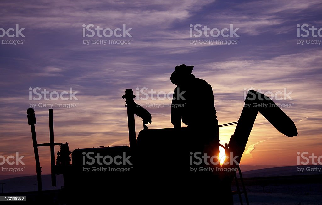 A black silhouette of a farmer on a tractor at sunset. stock photo