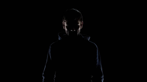 Black silhouette of mysterious man wearing hood, intention to commit crime Black silhouette of mysterious man wearing hood, intention to commit crime creepy stalker stock pictures, royalty-free photos & images