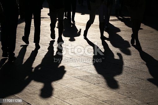 istock Black silhouettes and shadows of people on the street 1170511295
