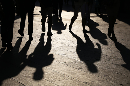 Black silhouettes and shadows of people on the street