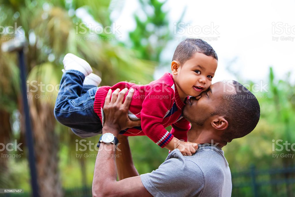Black single dad holding two year old son in air stock photo