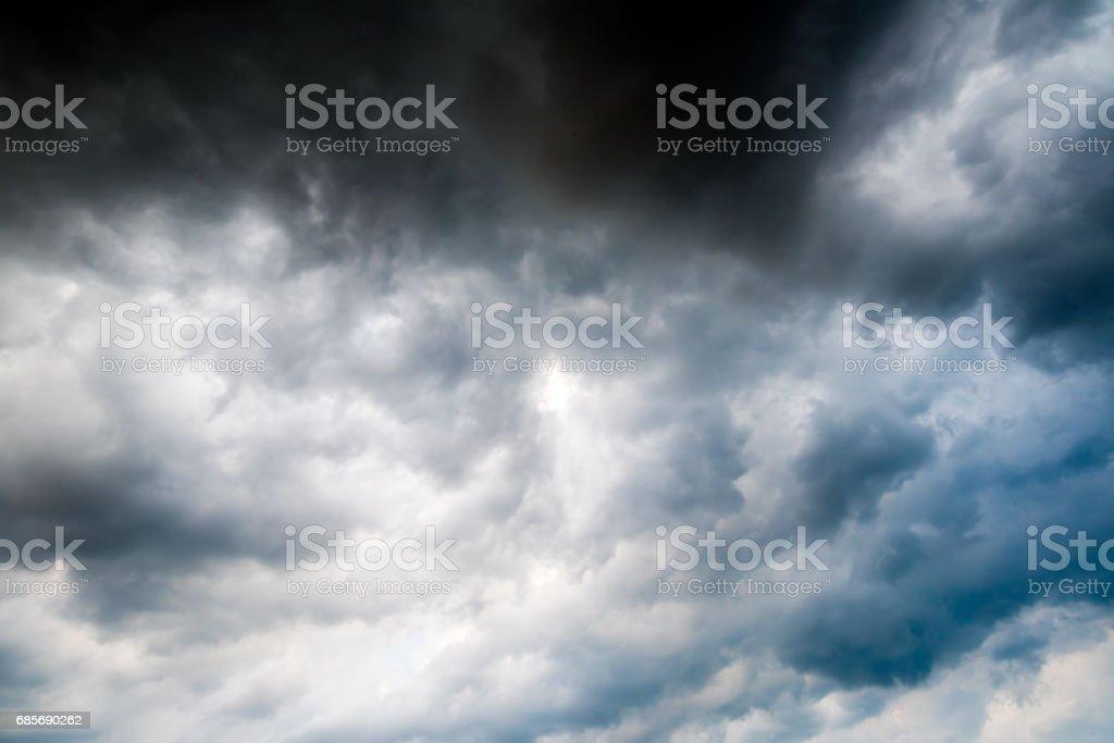 黑色的天空的烏雲雷鳴前的背景。陽光穿過黑暗的烏雲很黑暗的雲彩背景 免版稅 stock photo