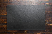black slate board on wooden background.