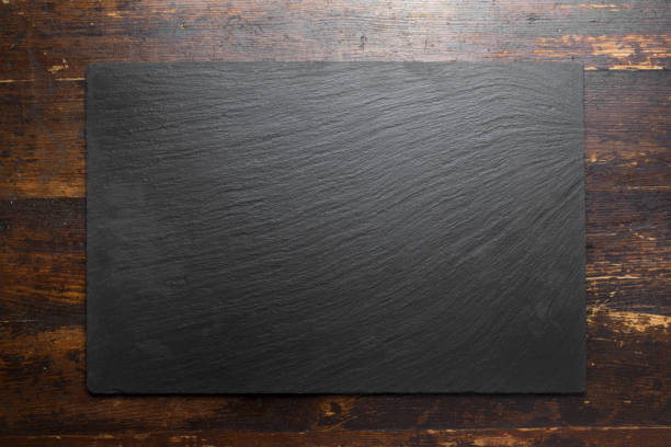 black slate board on wooden background. - разделочная доска стоковые фото и изображения