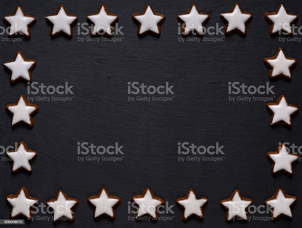 black slate board with star-shaped cookie frame stock photo